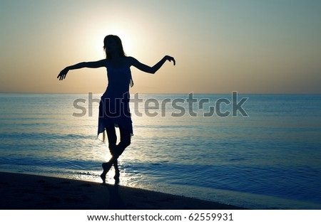 Silhouette of the woman doing relaxing dance exercise at the beach during sunset. Natural darnkess and colors - stock photo