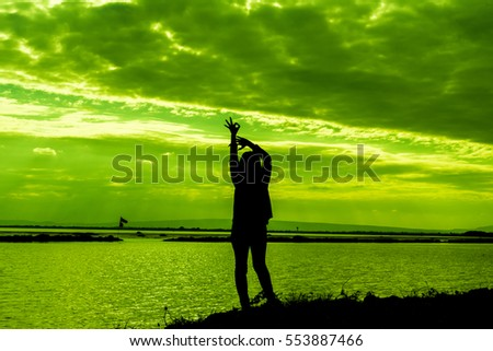 Silhouette of the woman standing at the lake