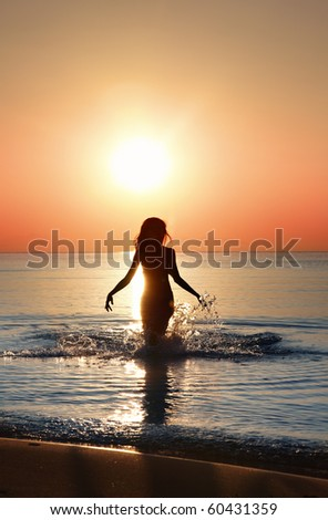 Silhouette of the woman walking in the water during beautiful sunrise. Natural light and darkness. Artistic vivid colors added - stock photo