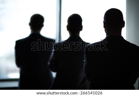 silhouette of three businessmen in the office - stock photo