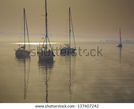 silhouette of three sail boats sitting on calm water - stock photo