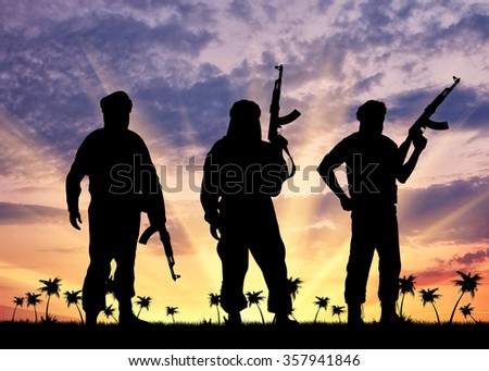 Silhouette of three terrorists with a weapon against a background of sunset and palm trees