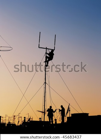 silhouette of three workers repairing communication antenna on the roof top full of TV and satellite antenna at sunset - stock photo