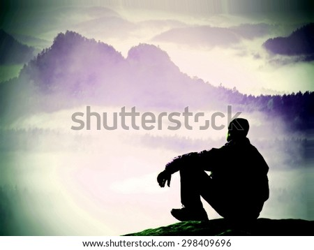 Silhouette of tired tourist in windcheater and dark cap sit on rock and watching into blue misty valley bellow. Sunny spring daybreak in rocky mountains. - stock photo