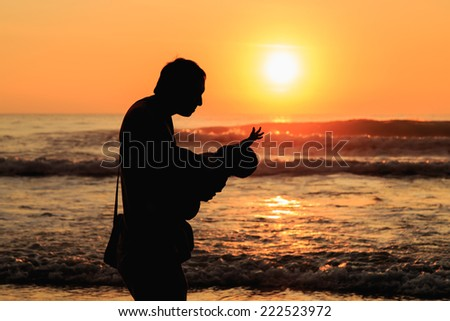 Silhouette of tourist at sunset beach in Phuket Thailand