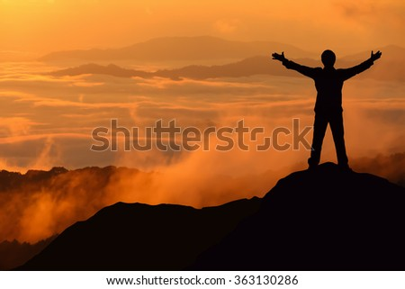 Silhouette of tourist man spread hand on top of a mountain enjoying morning mist at sunrise