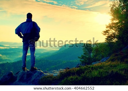 Silhouette of tourist. Sunny spring daybreak in rocky mountains. Hiker with sporty backpack stand on rocky view point above misty valley.  - stock photo