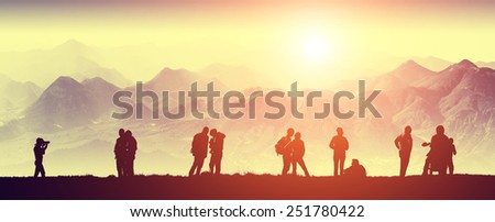 Silhouette of tourists in a high mountain valley. Travel team. Morning time. - stock photo