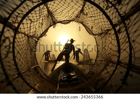 Silhouette of traditional fisherman in wooden boat on Inle lake with fog sunrise , Myanmar - stock photo