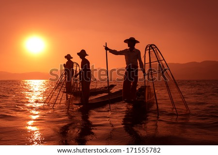 Silhouette of traditional fisherman in wooden boat using a coop-like trap with net to catch fish in Inle lake, Myanmar - stock photo