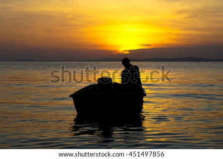 Silhouette of traditional fisherman on boat during beautiful sunrise at Labuan island,Malaysia.
