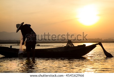Silhouette of traditional fishermen throwing net fishing lake at sunrise time,thailand (The casting people living along the River) - stock photo