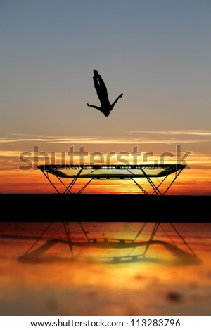 silhouette of trampoline gymnast on beach - stock photo