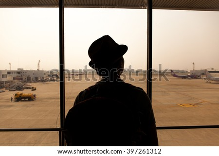 Silhouette of Traveler in Airport, waiting for the flight - stock photo