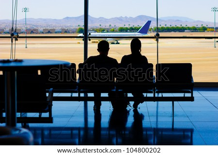 Silhouette of travelers in waiting area at airport with airplane visible on the runway outside - stock photo