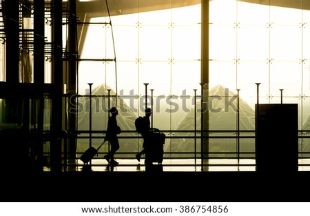 Silhouette of travelers is carry baggage to an Airport. sepia filter tone - stock photo