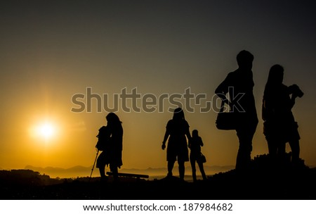 Silhouette of travelers with camera during sunrise on the mountain