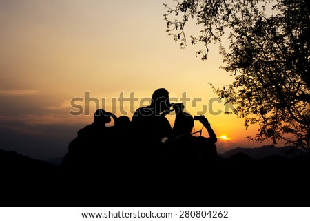 Silhouette of travelers with camera during sunset at That Phu Si and Wat tham Phu Si, Luang Prabang Laos.