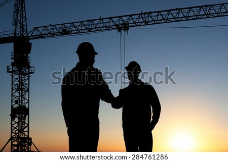 Silhouette Of Two Architect At Construction Site Shaking Hand - stock photo