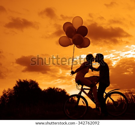 Silhouette of two beautiful adult people looking each other Young couple sitting at one bicycle Girl holding colorful balloons on sunset cloudy sky trees park background Copy space for inscription - stock photo