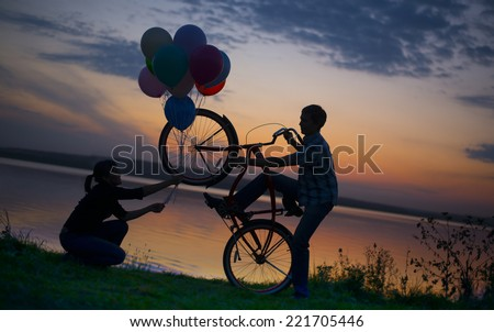 Silhouette of two beautiful couple Man sitting at one bicycle Woman holding give colorful balloons on sunset sky on Water in lake background Copy space for inscription Pair on date Birthday party