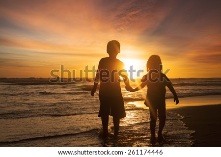Silhouette of two children walking on the beach while holding hands with sunset background on the back - stock photo