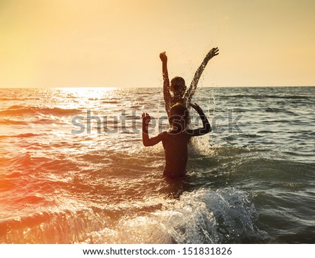 Silhouette of two happy little boy jumping in sea at sunset