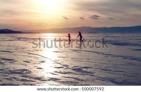 Silhouette of two ice skating people at lake Baikal frozen surface on sunset. Winter tourism concept