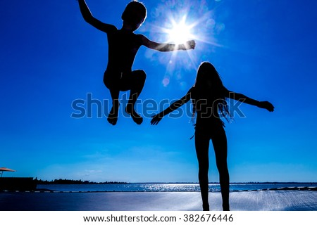 Silhouette of two kids jumping on trampoline against blue sky
