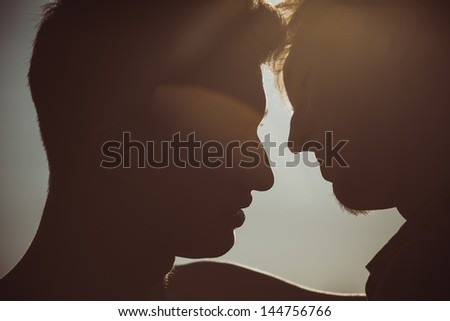 Silhouette of two men about to kiss - stock photo