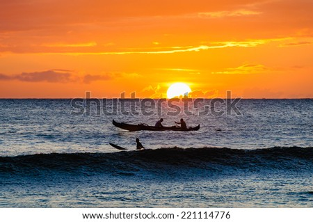 Silhouette of two men paddling a Hawaiian outrigger canoe at sunset, Maui, Hawaii, USA - stock photo