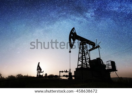 Silhouette of two oil pumps are extracting crude oil on the oil field under night sky with stars. Petroleum industry equipment. Milky way shines above - stock photo