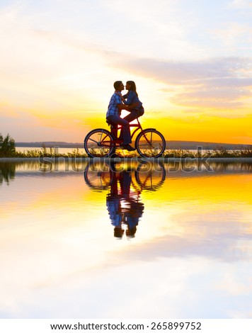 Silhouette of two people  looking each other on date Cute couple sitting at one bicycle Girl embracing boyfriend on sunset cloudy sky trees park and water in lake background Copy space for inscription - stock photo