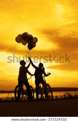 Silhouette of two people on romantic date looking each other Young couple sitting at one bicycle Girl holding colorful balloons on sunset cloudy sky trees park background Copy space for inscription