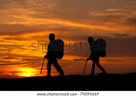silhouette of two walking rock climbers on sunset sky - stock photo