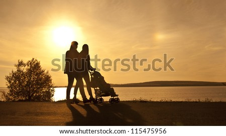 Silhouette of two women walking with a perambulator.