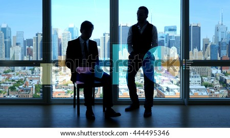 silhouette of two young professionals having a business meeting talking about financial strategies. sales progress development charts background