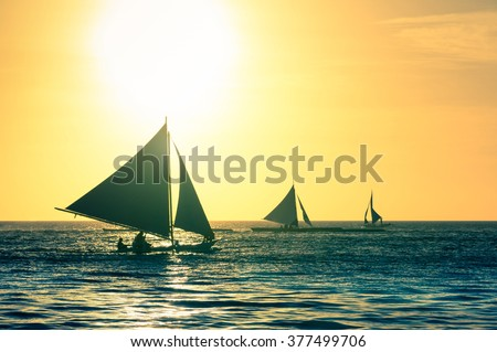 Silhouette of typical sailing boats at sunset in Boracay island - Exclusive travel destination in Philippines - Warm vintage filtered look - stock photo