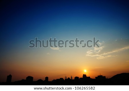 silhouette of urban skyline isolated on orange sunset and blue sky view - stock photo