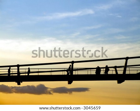 Silhouette of walking people and pedestrian bridge - stock photo