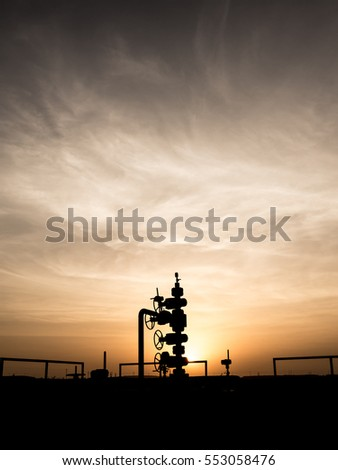 Silhouette of wellhead assembly on oil well in oilfield