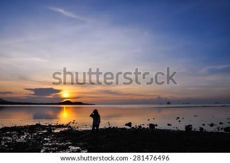 Silhouette of weman stand on sunset beach in Koh Samui, Thailand - stock photo