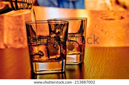 silhouette of whiskey glasses with ice on bar table on warm atmosphere lounge bar concept - stock photo