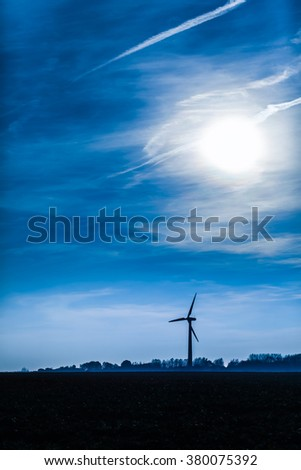 Silhouette of wind generator and horizon with dramatic twilight sky/Facility of Natural Energy - stock photo