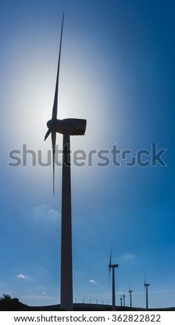 silhouette of wind turbine against blue sky