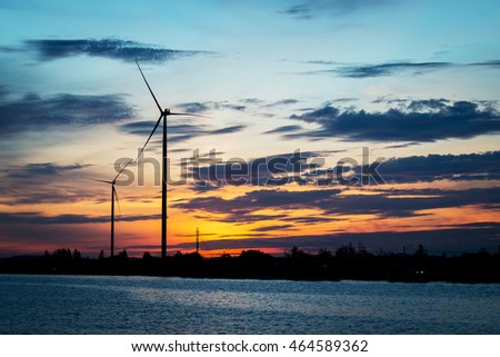 Silhouette of wind turbine at river background