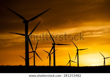 Silhouette of wind turbines generating electricity. - stock photo