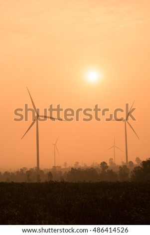 silhouette of wind turbines power generator at sunset