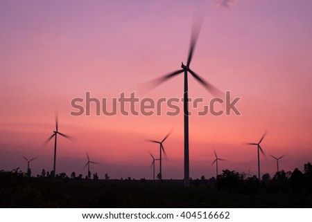 silhouette of wind turbines spinning at twilight - stock photo