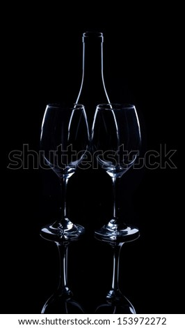 Silhouette of wine bottle and glass on black mirror.